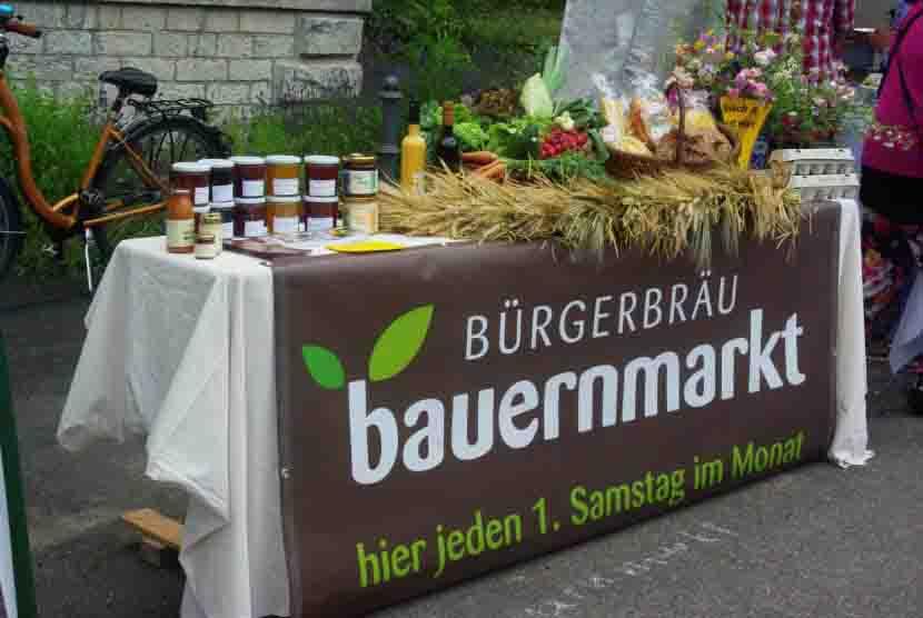 Bauernmarkt im Bürgerbräu September 2021 Tisch mit Banner und Dekoration mit Produkten der Beschicker