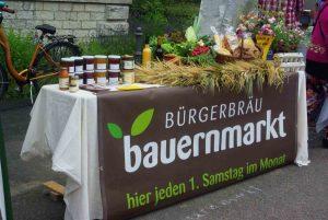 Tisch mit Banner mit der Aufschrift Bauernmarkt im Bürgerbräu Würzburg, dekoriert mit Waren der Beschicker