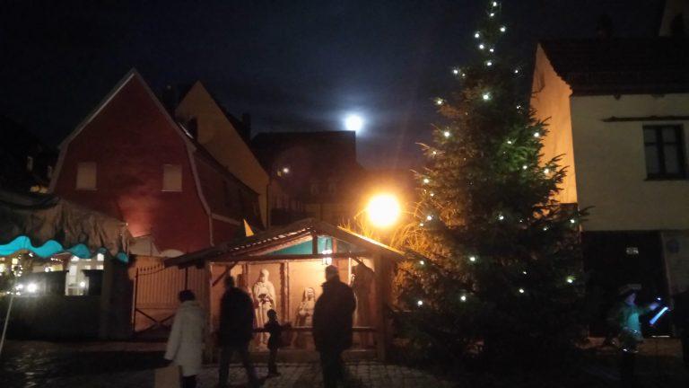 Weihnachtlich geschmückter Stand, beleuchtet und am Himmel der volle Mond