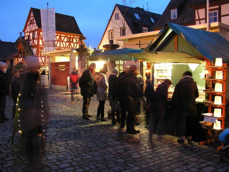 Marktbude weihnachtlich geschmückt und beleuchtet in der Dämmerung in Sommerhausen