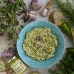 Gartenkräuterbutter mit frischen Kräutern, angerichtet auf einem türkisfarbenem Teller, umrahmt von frischen Kräutern und einem Glas Pesto di Limone