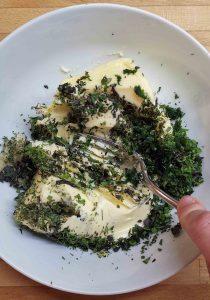 Für die Kräuterbutter wird zimmerwarme Butter mit den fein gehackten Kräutern mit der Gabel vermischt