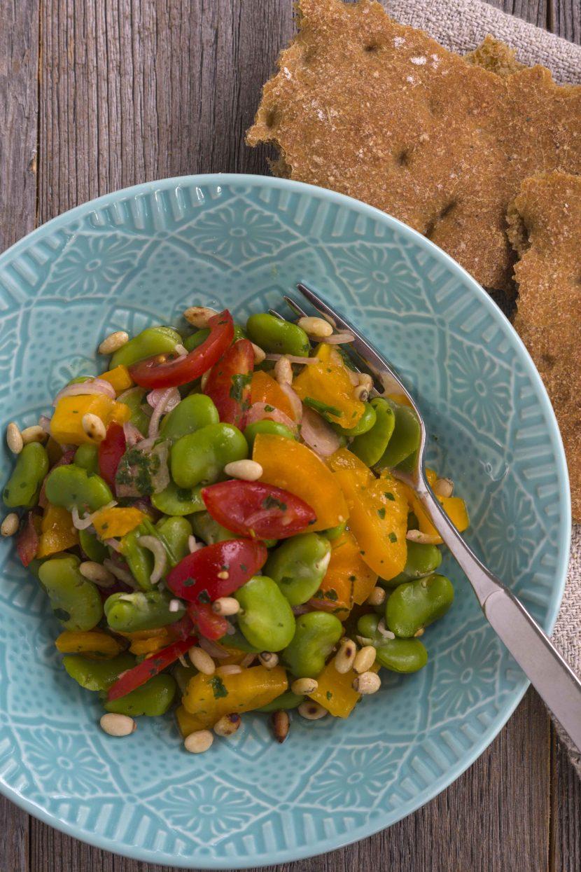 Salat aus dicken grünen Bohnen angerichtet mit Tomaten, Schalotten und Pinienkernen