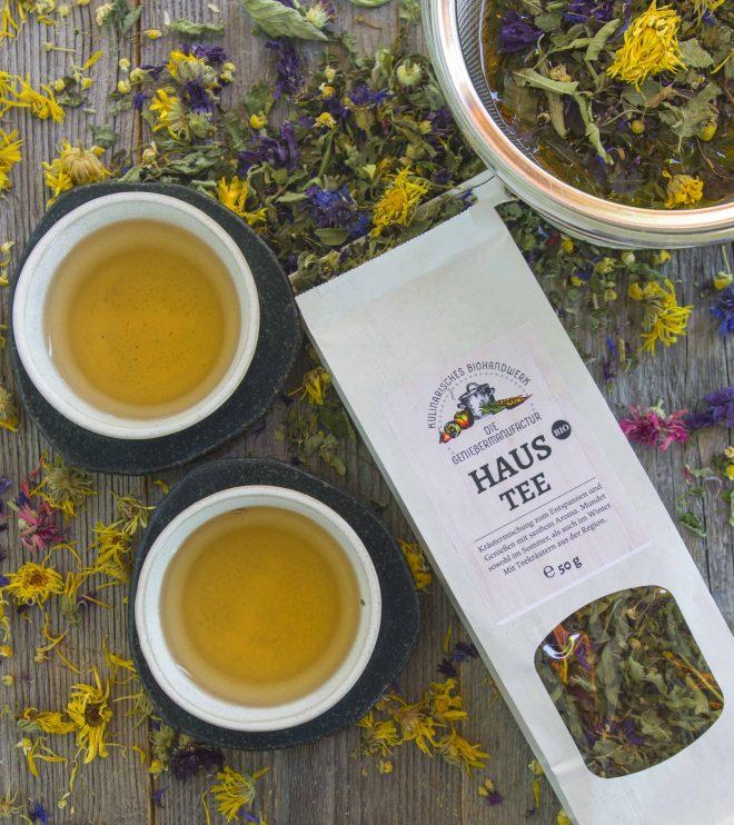 Kräuter-Haustee in einer weißen Verpackung mit Fenster. Viele Kräuter liegen auf einem Holzuntergrund, darauf zwei Tassen Tee und eine Glaskanne mit den ziehenden Kräutern und Blüten.