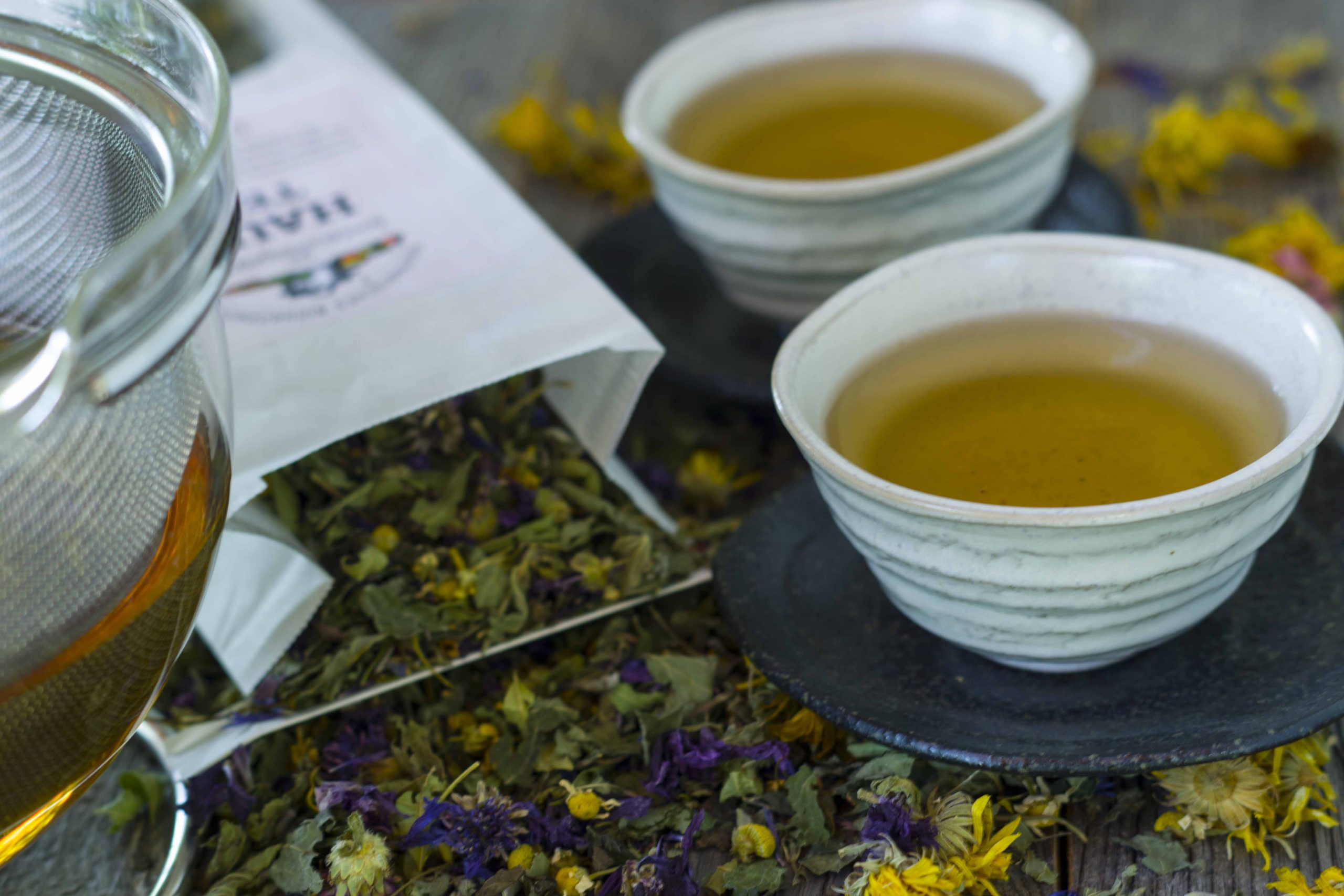 Kräuter-Haustee Bio im Aufguss in zwei Tassen. Untergrund Holz mit aufgestreuten Teezutaten, einer offenen Packung und einer großen Glaskanne mit Siebeinsatz.
