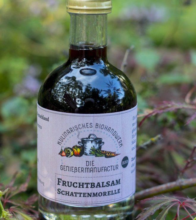 Fruchtbalsam Schattenmorelle bio in einer kleinen Flasche mit Logo der Genießermanufactur und Titel auf weißem Hozhintergrund